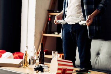 cropped view of man standing and showing empty pockets after party