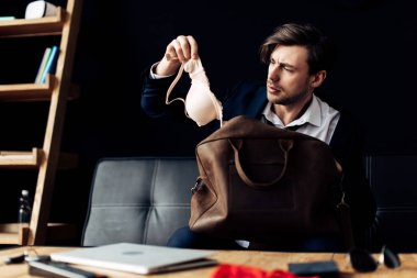 confused man in suit looking at bra after party in office