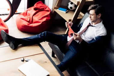 man in suit holding pink panties while sitting on sofa after party in office