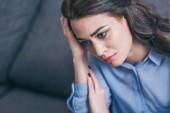smutná žena v modrá halenka sedí na gauči šedé a drží hlavu v místnosti, truchlící porucha koncept