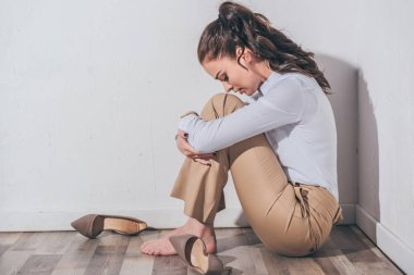 sad woman in white blouse and beige pants sitting on floor with head bent near white wall at home, grieving disorder concept