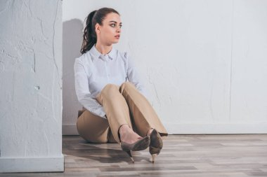 upset woman in white blouse and beige pants sitting on floor near white wall at home, grieving disorder concept