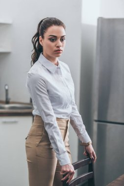 upset woman in white blouse and beige pants standing by chair in kitchen, grieving disorder concept