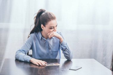 upset woman in blue blouse sitting at table with photo and thinking in room, grieving disorder concept