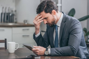 sad man in gray suit sitting at wooden table with smartphone, white cup, looking at photo in frame and thinking at home, grieving disorder concept