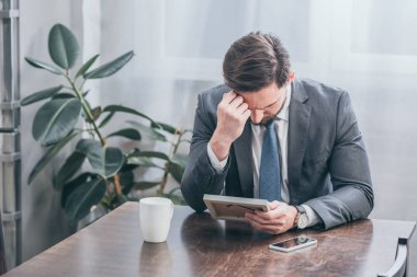 sad man in gray suit sitting at wooden table with smartphone, white cup and holding photo frame at home, grieving disorder concept