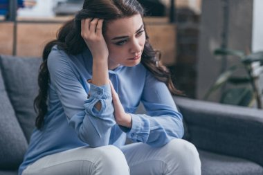 sad woman in blue blouse sitting on grey couch and looking into distance at home, grieving disorder concept