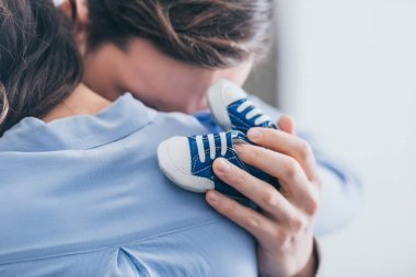 cropped view of man hugging woman and holding blue baby shoes in room, grieving disorder concept