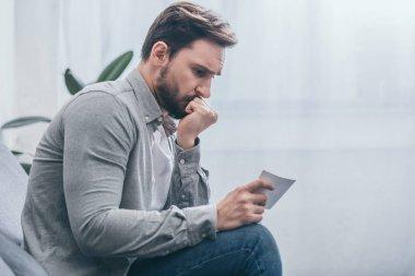 sad man sitting and loking at photo at home, grieving disorder concept