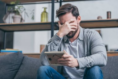 upset man in gray shirt covering face with hand and holding photo frame at home, grieving disorder concept