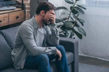 man sitting on couch and crying at home, grieving disorder concept