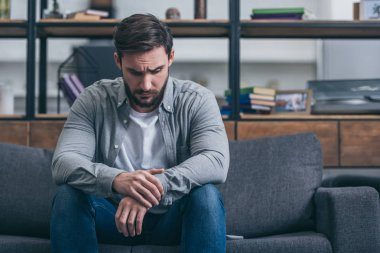 depressed man sitting and grieving on couch in living room