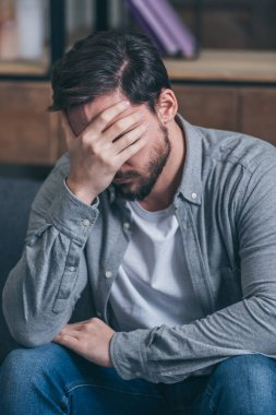 upset man sitting, crying and covering face with hand at home