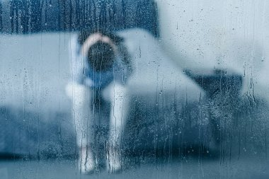 depressed woman sitting on bed and holding head in hands through window with raindrops