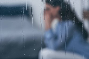 selective focus of raindrops on windows with sad woman sitting on background
