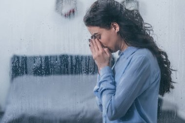 depressed woman covering face with hands and crying at home through window with raindrops and copy space