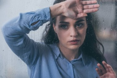 beautiful upset woman looking away and touching window with raindrops