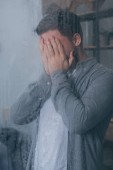 Fotografie Erwachsener Mann bedeckt Gesicht mit Händen und weint durch Fenster mit Regentropfen