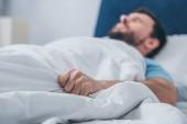Fényképek ember az ágyban fekve, és a gazdaság takaró
