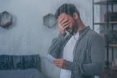 depressed man covering face with hand, holding photograph and crying through window with raindrops