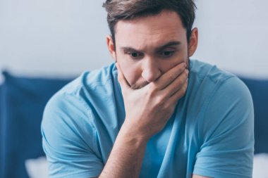 selective focus of stressed man covering mouth with hand at home