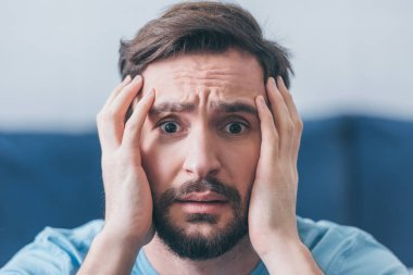 selective focus of frightened man with hands on head looking at camera at home