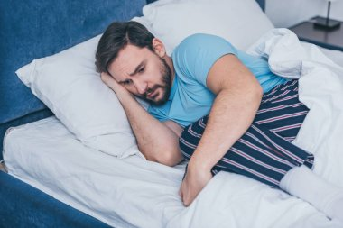 sad man in pajamas grieving while lying in bed alone