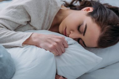 beautiful tired woman hugging pillow and sleeping in bed at home