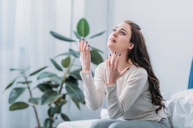 frustrated woman gesturing with hands and grieving at home