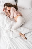 Fotografie Top view of pregnant woman sleeping in bed