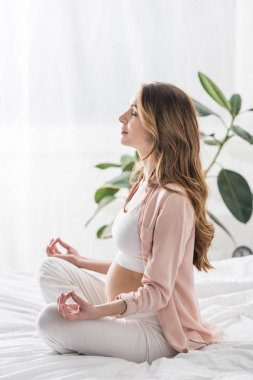 Long-haired pregnant woman meditating with closed eyes in bed