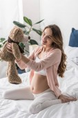 Smiling pregnant woman playing with toy bear in bed