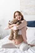Dreamy pregnant woman embracing toy bear with closed eyes