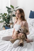 Attractive pregnant woman sitting on bed with toy bear