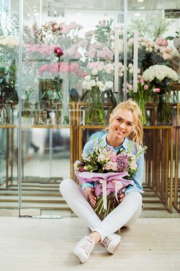 beautiful smiling woman holding flower bouquet while sitting in front of flower shop with copy space