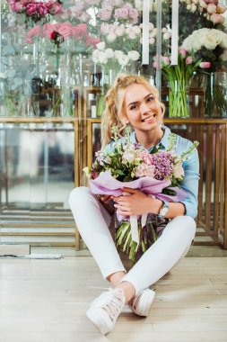 beautiful smiling woman holding flower bouquet, looking at camera and sitting in front of flower shop
