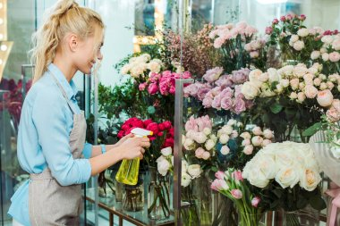 female florist in apron spraying flowers with spray bottle in flower shop