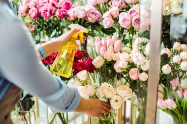 cropped view of female florist spraying flowers with spray bottle in flower shop
