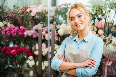 Beautiful smiling female florist in apron looking at camera with flower shop on background stock vector