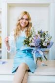 szép mosolygó nő virág üzlet tulajdonosa ül a csokor, látszó-on fényképezőgép és gazdaság üzleti kártya-val másol hely