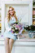 Fotografie krásný usměvavý majitel květinářství při pohledu na fotoaparát, sittng na pult a držení kytice