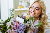 Fotografie beautiful smiling woman holding flower bouquet with roses, lilac and card with copy space