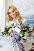 Fotografie selective focus of beautiful smiling woman with flower bouquet with roses, lilac and blank card on foreground