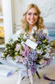 Fotografie selective focus of flower bouquet with roses, lilac and blank card with woman on background