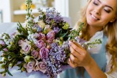 Fotografie smiling female florist arranging bouquet with lilac and roses in flower shop