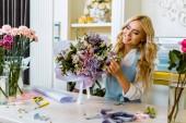 Fotografie schöne weibliche Florist Schürze, die Vermittlung von Strauß in Blumenladen lächelnd