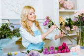 attractive female florist in apron arranging bouquet with roses in flower shop