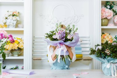 female florist holding bouquet in front of face at counter in flower shop