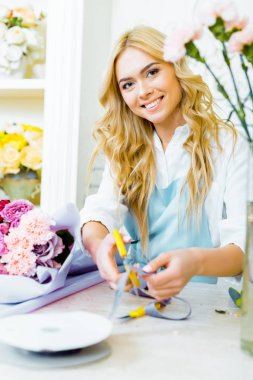 beautiful female florist looking at camera and cutting ribbon with scissors in flower shop