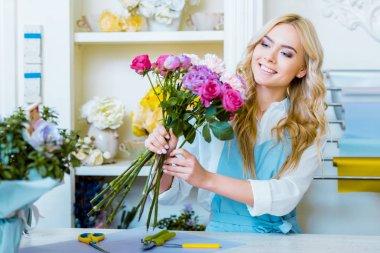 beautiful smiling female florist arranging bouquet in flower shop